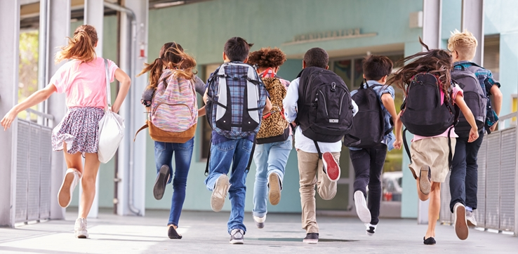 Home Comfort-children wearing backpacks running down school hallway